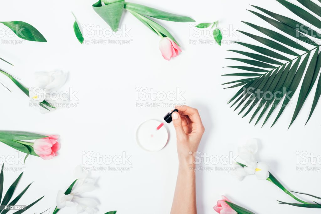 Flat lay woman's hand dripping cosmetic fluid stock photo