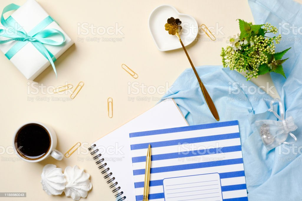 Flat lay women workspace with coffee cup, marshmallow, paper notebook...