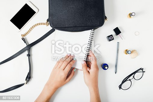 istock Flat lay women workspace with female hands, bag, notebook, smartphone, glasses and nail polish 831932306