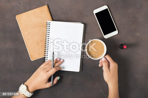 831932306 istock photo Flat lay women workspace with female hands, cup of coffee, notebook, smartphone with a blank screen and lipstick 831537426