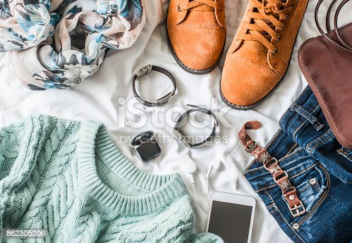 istock Flat lay women's clothing for autumn walks, top view. Brown suede boots, jeans, a blue pullover, scarf, bracelets, watches, headphones, perfume and bag on a light background. Fashion concept 862305206