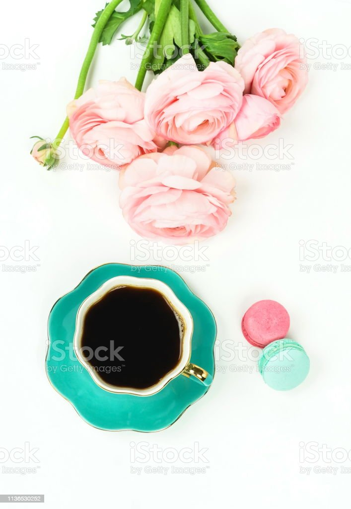 Flat lay women\'s desk with cup of coffee and flowers pink ranunkulus,...