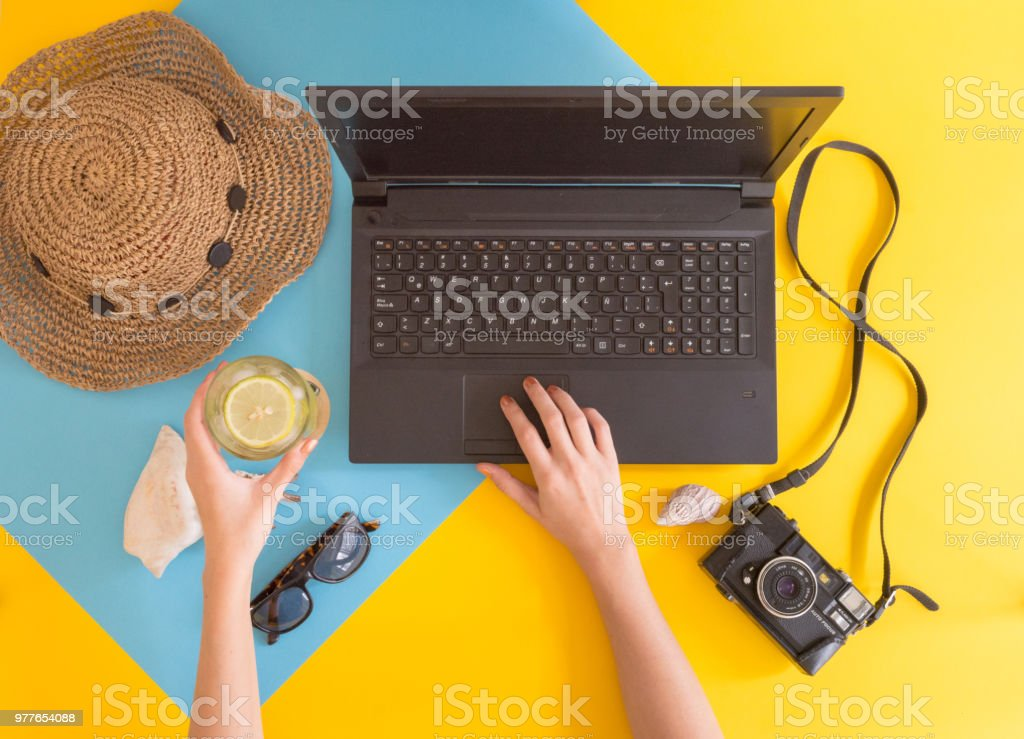 Flat lay work and travel, beach and tropical theme, with young women hands and copy space for text. stock photo