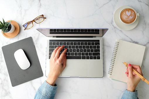 Flat lay workspace. Woman hand with coffee cup, smartphone, computer, notebook, planner and stationary with copy space on marble table background. Top view. modern style.