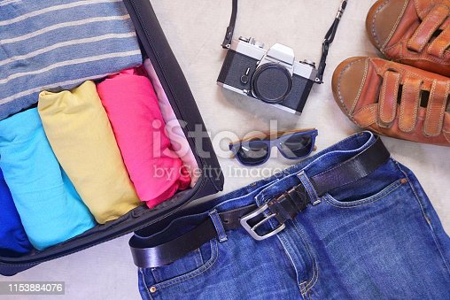 Flat layout open travel bag with sunglasses and camera and blue jeans and leather shoes on gray background.