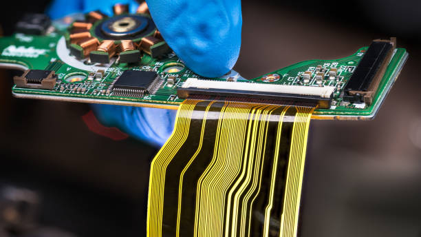 Flat plastic strip flexible cable on printed circuit board on a dark background stock photo