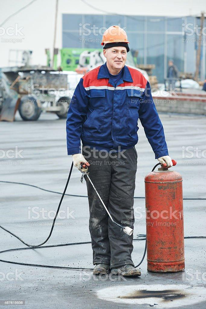 Flat roof covering repair worker stock photo