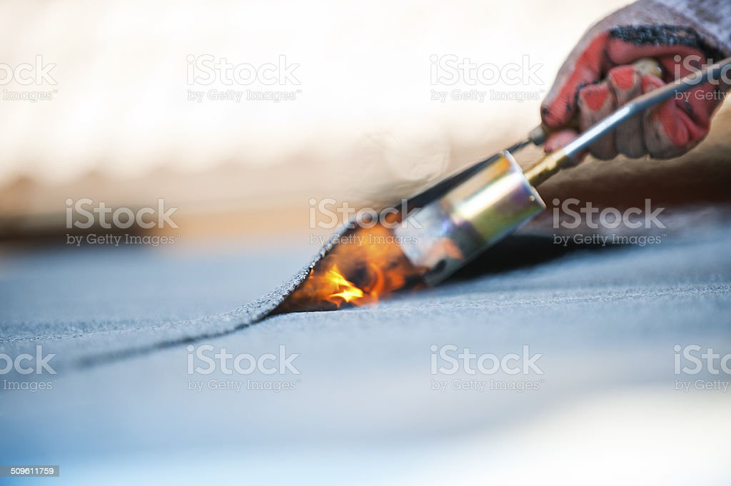 Flat roof covering works with roofing felt stock photo