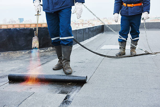 Flat roof installation. Heating and melting bitumen roofing felt stock photo