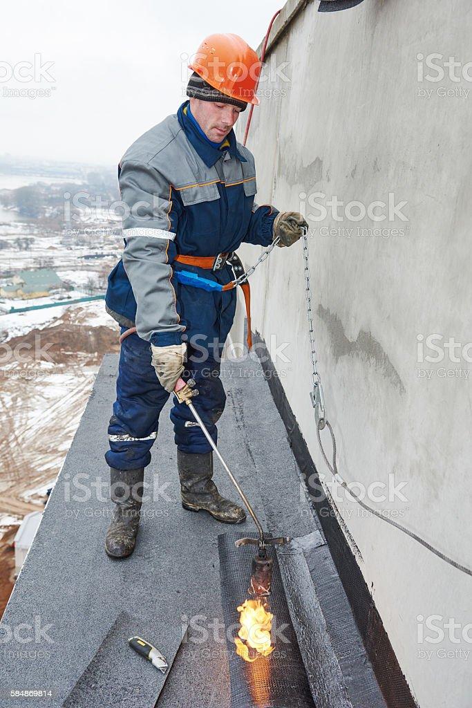 Flat roof installation. Workers melting bitumen roofing felt stock photo