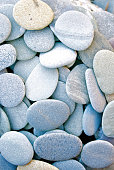 A vertical composition of flat round pebbles.