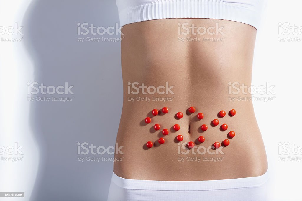 A flat stomach with SOS in red bubbles royalty-free stock photo