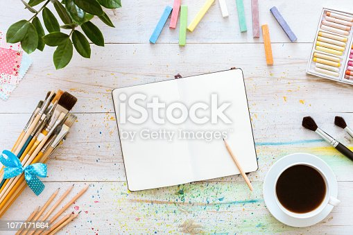 istock Flat style artistic design workspace, blank notebook mock up for creative sketches with watercolor paints, pencil, set of paintbrushes and cup of coffee on white wooden table, top view, copy space 1077171664
