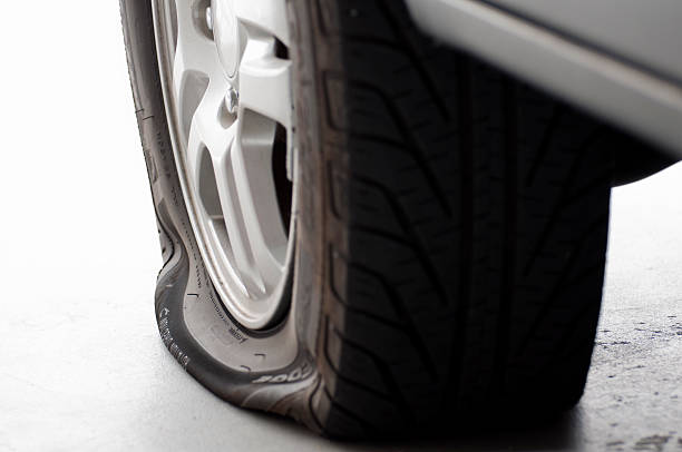 A flat tire is the focus isolated on white stock photo