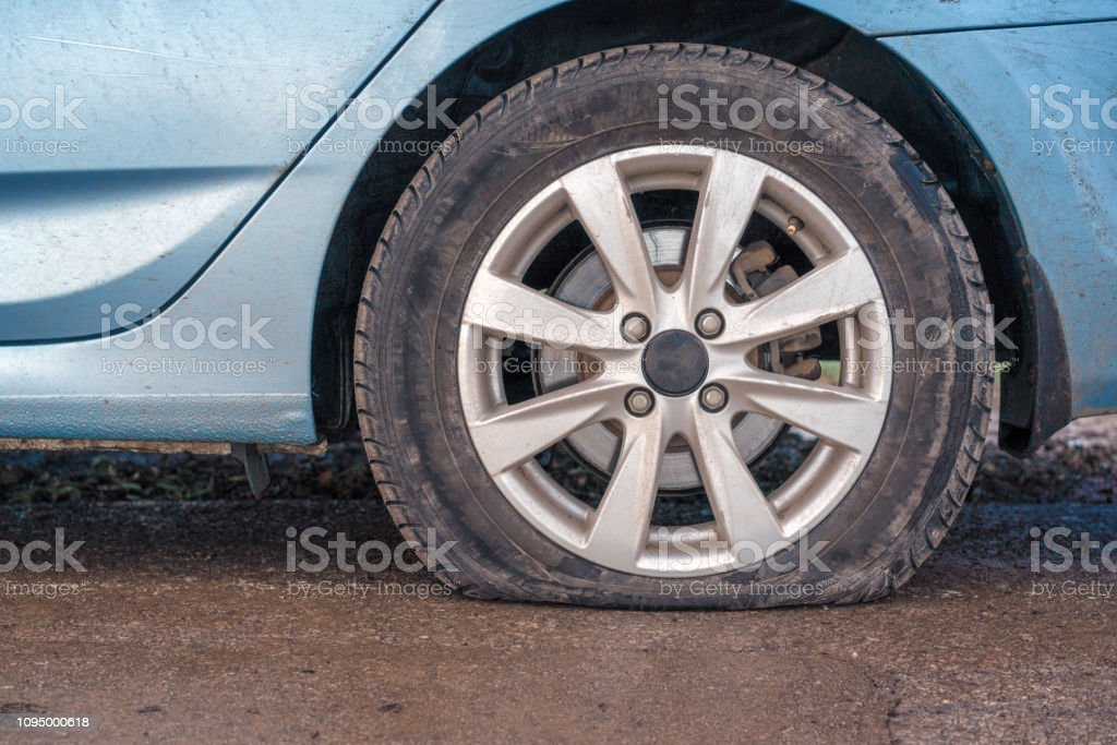 Flat tire of blue car on the road waiting for repair stock photo