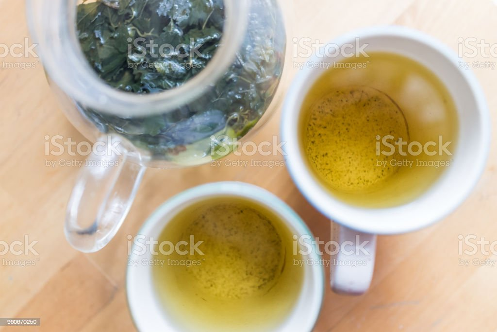 Flat top flat lay view looking down below closeup of two cups with green tea or jiaogulan, gynostemma herbal tea on wooden table with hot steam, leaves stock photo