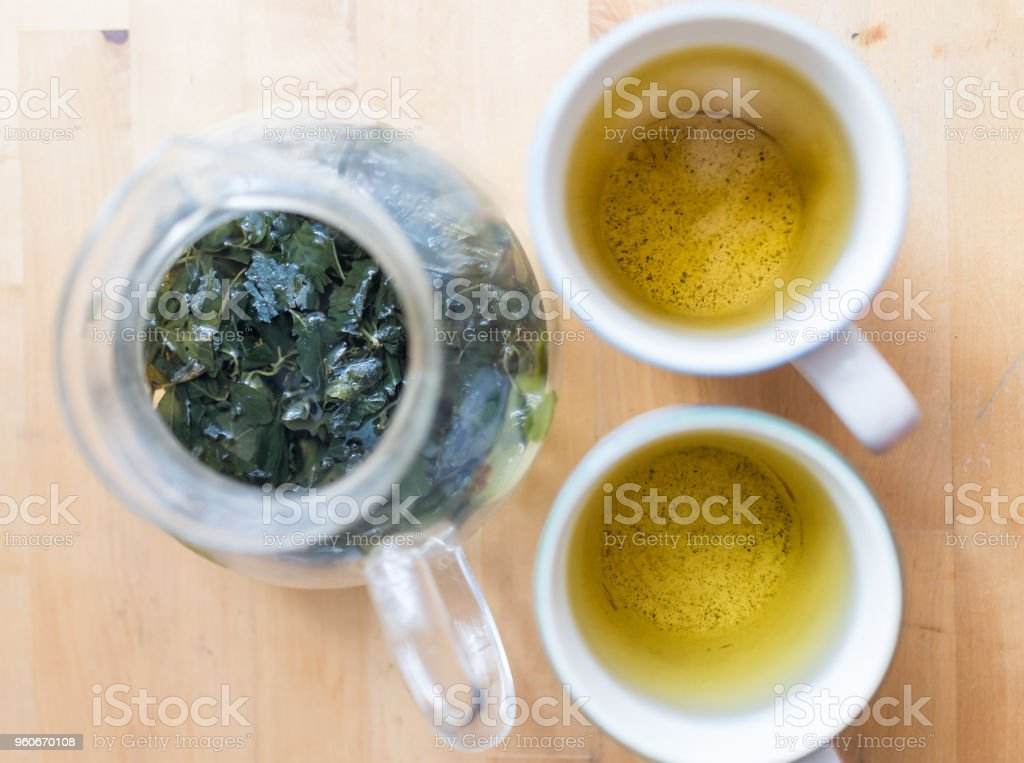 Flat top flat lay view looking down below of two cups with green tea or jiaogulan, gynostemma herbal tea on wooden table with hot steam, leaves stock photo