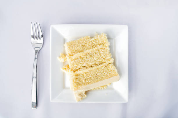flat top table setting lay view down closeup of restaurant or wedding reception white table tablecloth one plate with vanilla cream cake slice, fork - кусок торта стоковые фото и изображения