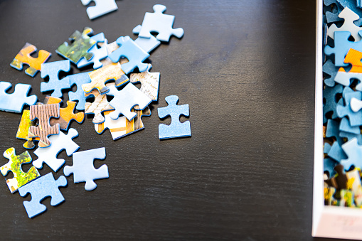 Flat top view of puzzle pieces on table scattered as game in room of house and box