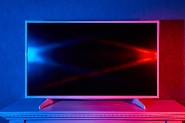 un téléviseur allumé avec des couleurs rouges et bleus - imitant un animal photos et images de collection