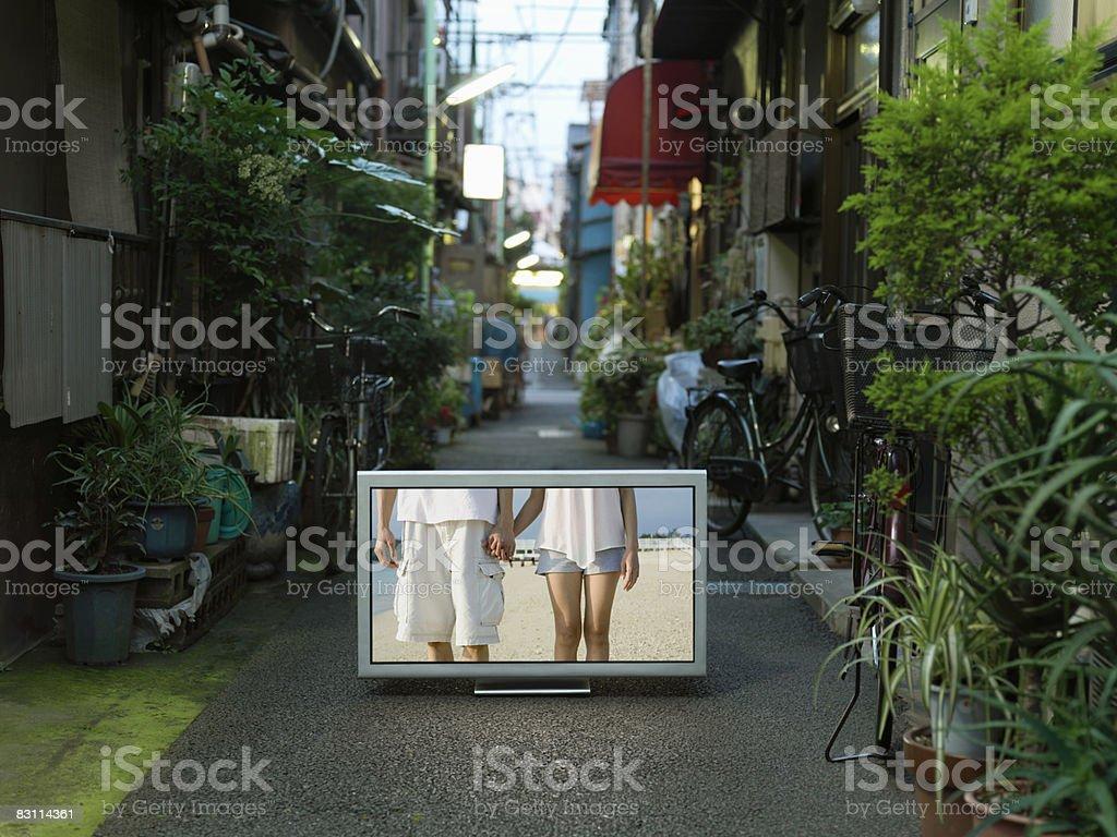 Flat TV placed on urban alley royaltyfri bildbanksbilder