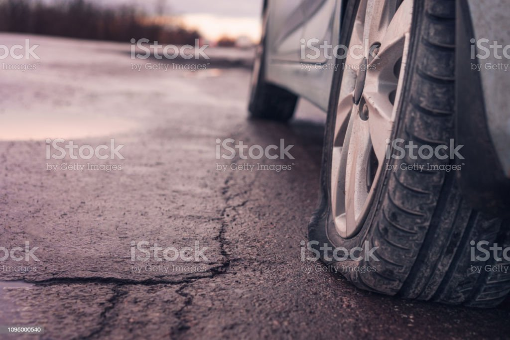 Flat tyre on road. Car tire leak because of nail pounding. Toned stock photo