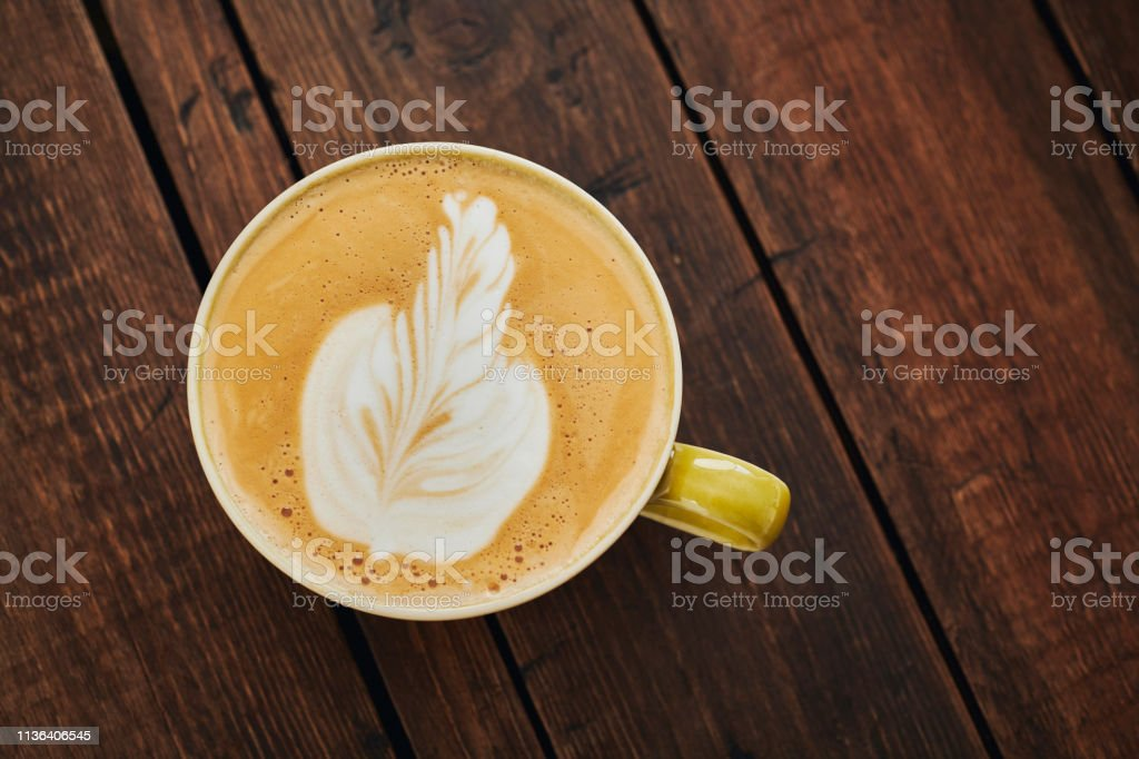 Flat White Coffee in a green cup on a dark aged rustic wood table. stock photo