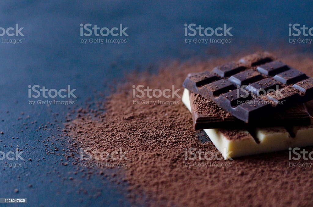 Flat with milk, black and white chocolate on a black background....