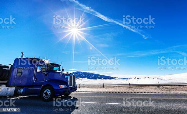 Photo of Flatbed Semi Trailer Truck Driving on Western USA Sunflare Expressway