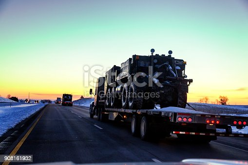 istock Flatbed Semi Truck Convoy Hauling Armored Military Land Vehicles 908161932