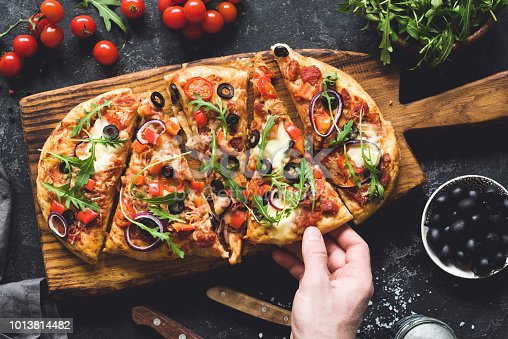 istock Flatbread pizza garnished with fresh arugula on wooden pizza board, top view 1013814482