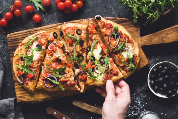 fladenbrot pizza garniert mit frischen rucola auf hölzernen pizza brett, ansicht von oben - fladenbrotpizza stock-fotos und bilder