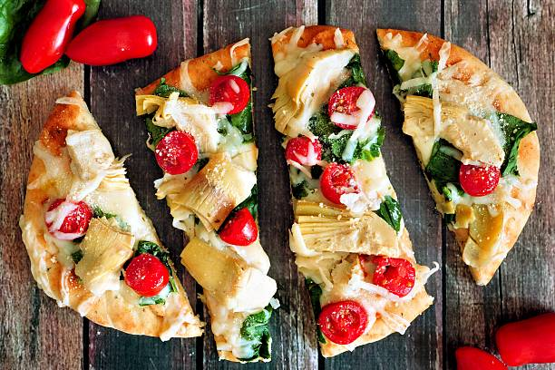 flatbread pizza with mozzarella, tomatoes, spinach, artichokes, over rustic wood - fladenbrotpizza stock-fotos und bilder