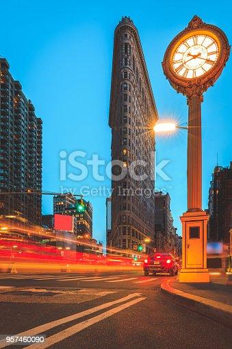 Traffic blurs past the Flatiron Building during twilight.