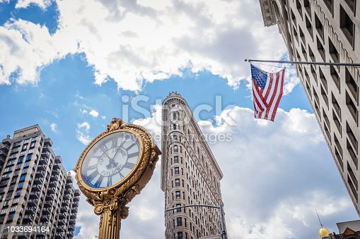Flatiron building with golden clock in New York city