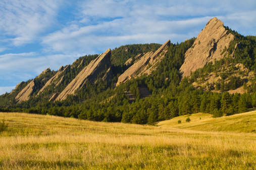 The early morning light hitting the Boulder Colorado flatirons. The Flatirons are rock formations in Boulder, Colorado consisting of flatirons. There are five large, numbered Flatirons ranging from north to south (First through Fifth, respectively) along the east slope of Green Mountain, and the term