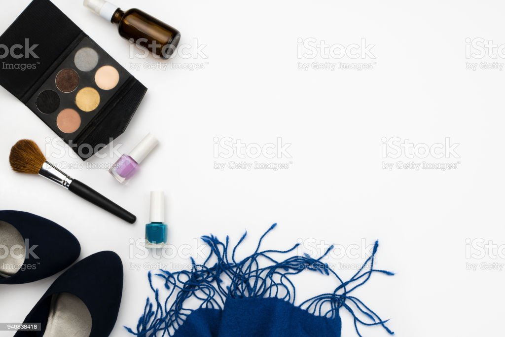 Flatlay arrangement with blue high heeled shoes, cosmetic palette, brush, nail polish and blue scarf, fashion concept, white background, copyspace stock photo