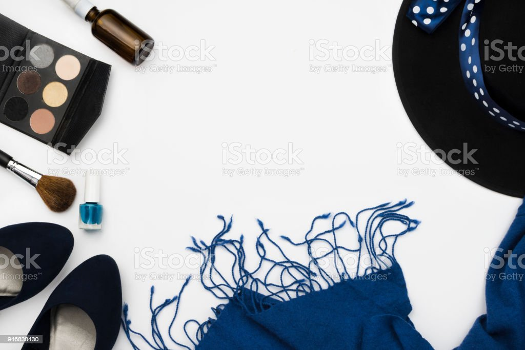 Flatlay arrangement with blue high heeled shoes, cosmetic palette, brush, nail polish, blue scarf and hat, fashion concept, white background, copyspace stock photo