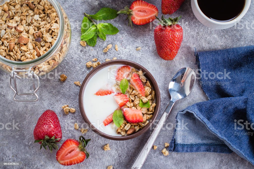 Flat-lay Food Concept. Yogurt, granola and strawberries on gray concrete table background. Top view. Healthy Food - Royalty-free Antioxidant Stock Photo