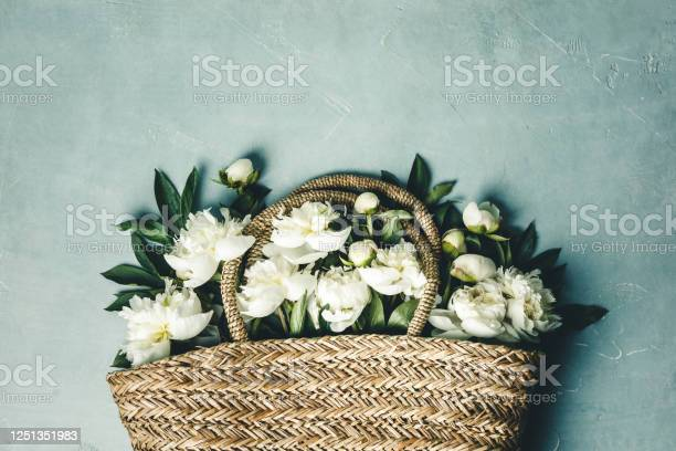 Flatlay of beautiful peony flowers in straw bag over blue rustic picture id1251351983?b=1&k=6&m=1251351983&s=612x612&h=sc2quqqirrruzon0byeibaocbstf8xswbt1qtliehwq=