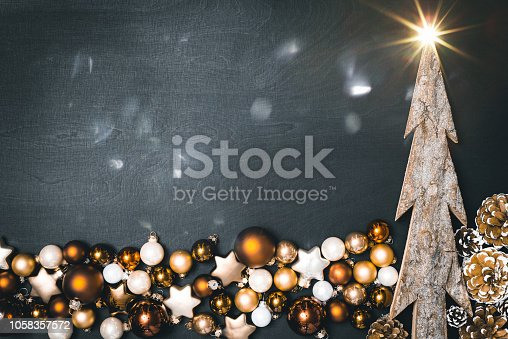 istock Flatlay of christmas concept with baubles and tree and blank space in front of black background 1058357572