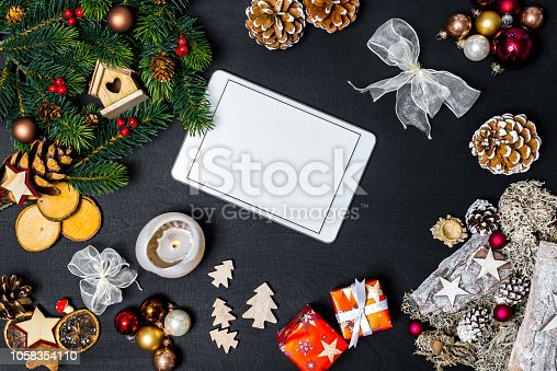 istock Flatlay of christmas concept with white tablet and blank space with black background 1058354110