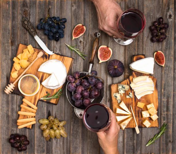 Wohnung-Lay von paar oder mit Freunden genießen Wein, Essen und trinken zusammen. Draufsicht der Leute, die party, feiern am rustikalen Holztisch. Käseplatte mit Wein, Trauben, Feigen und Honig serviert. Hände halten Gläser. – Foto