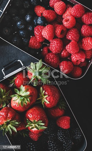 517278430 istock photo Flat-lay of fresh berries in lunchboxes over dark background 1214868572