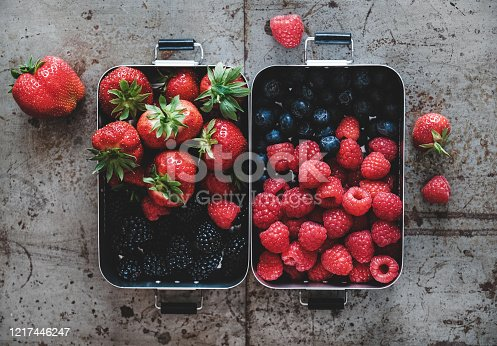 517278430 istock photo Flat-lay of fresh berries in lunchboxes over rough grey background 1217446247