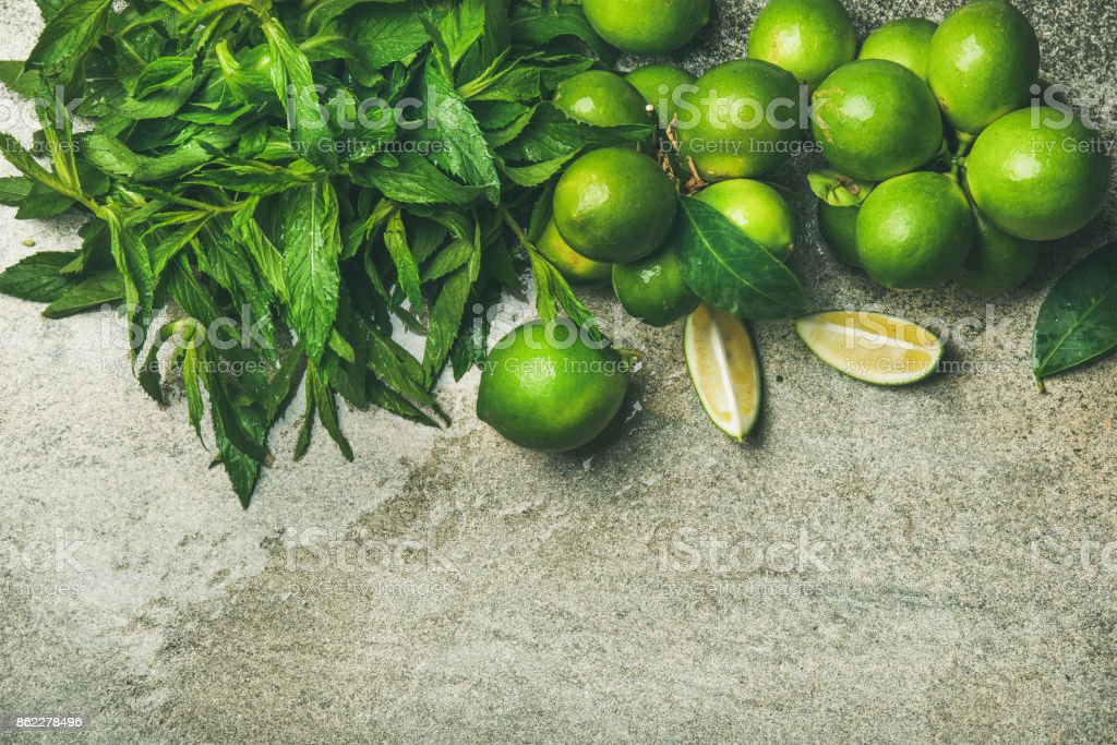 Flatlay of freshly picked limes and mint for making cocktail stock photo