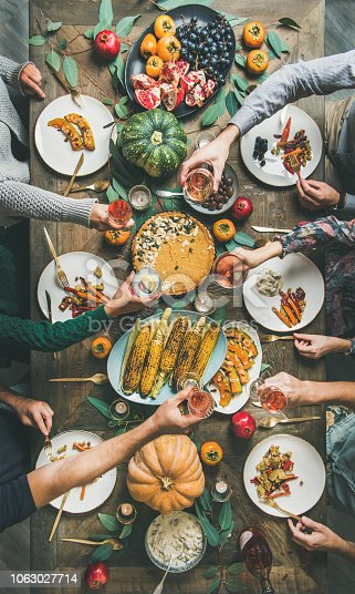istock Flat-lay of Friends clinking glasses at Thanksgiving Day, vertical composition 1063027714