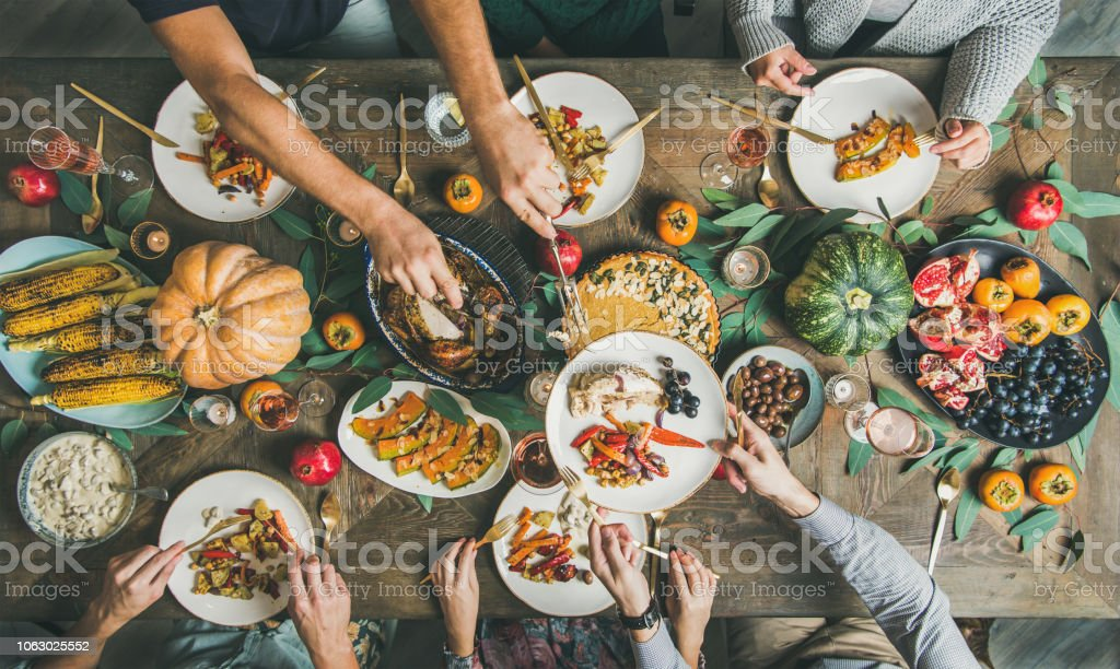 Flat-lay of friends feasting at Thanksgiving Day table with turkey stock photo