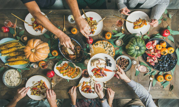 flat-lay of friends feasting at thanksgiving day table with turkey - family dinner stock photos and pictures
