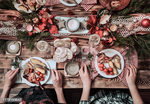 istock Flat-lay of friends hands eating and drinking together. Top view of people having party, gathering, celebrating together at wooden rustic table 1173193647